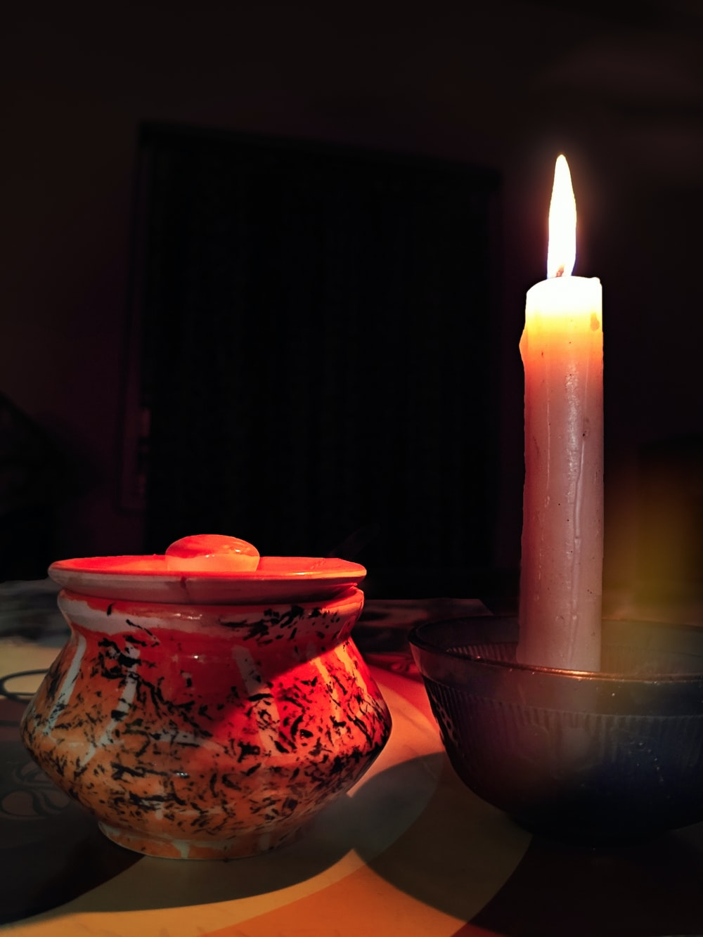 red ceramic pot beside taper candle