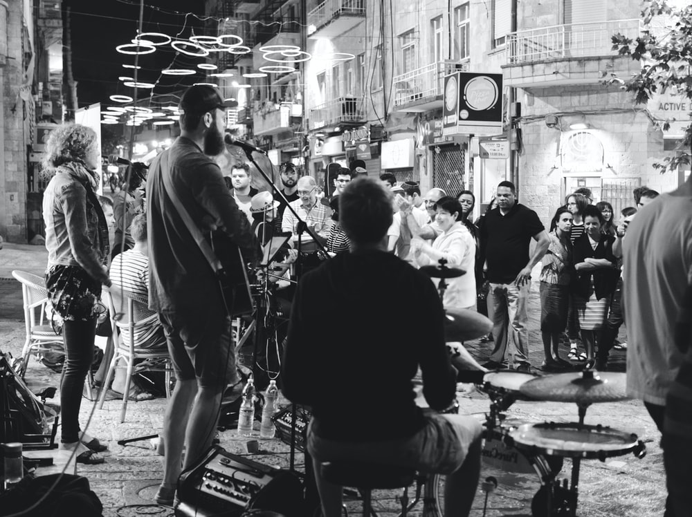 grayscale photo of people performing on street