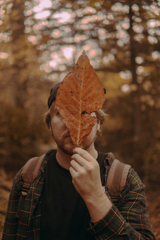 man wearing black bennies holding brown leaf