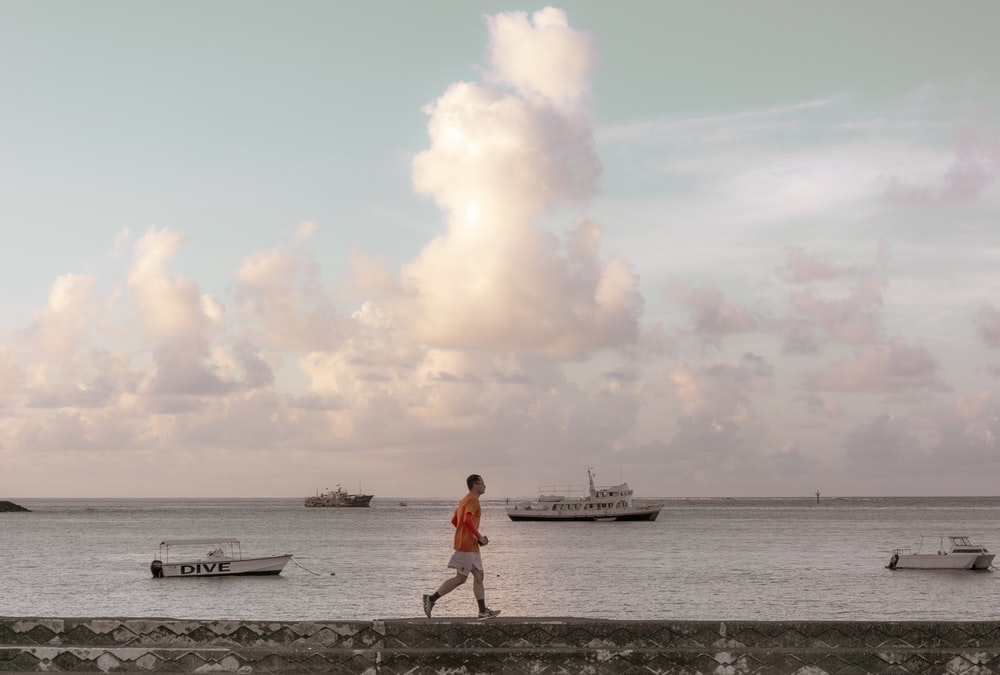 man walking on bay