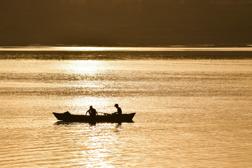 silhouette of two person on boat