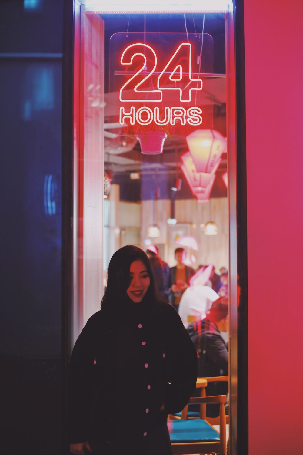 woman near 24 hours neon sign