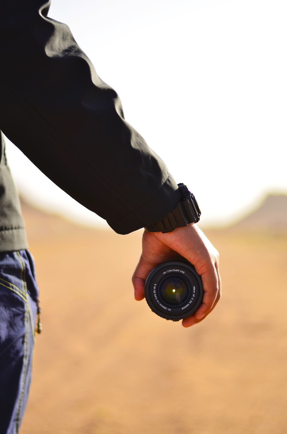 person holding DLSR camera lens