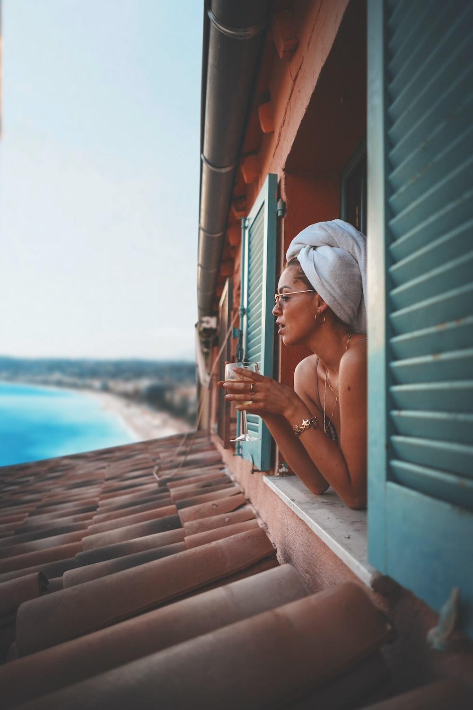 woman on window holding glass