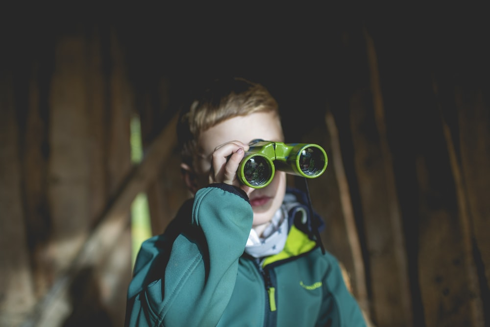 boy using green binoculars