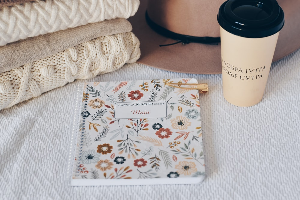 white and multicolored floral notepad by coffee cup