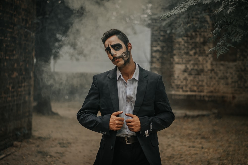 man wearing black notched lapel suit jacket with Halloween art on face standing