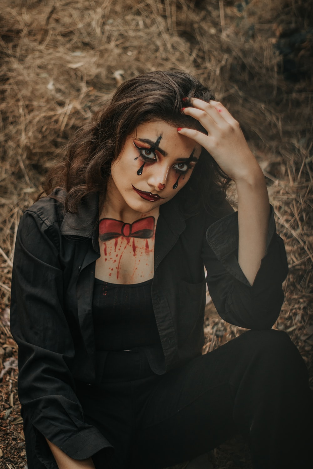 woman wearing black collared button-up long-sleeved shirt with Joker paint on face sitting while touching her head