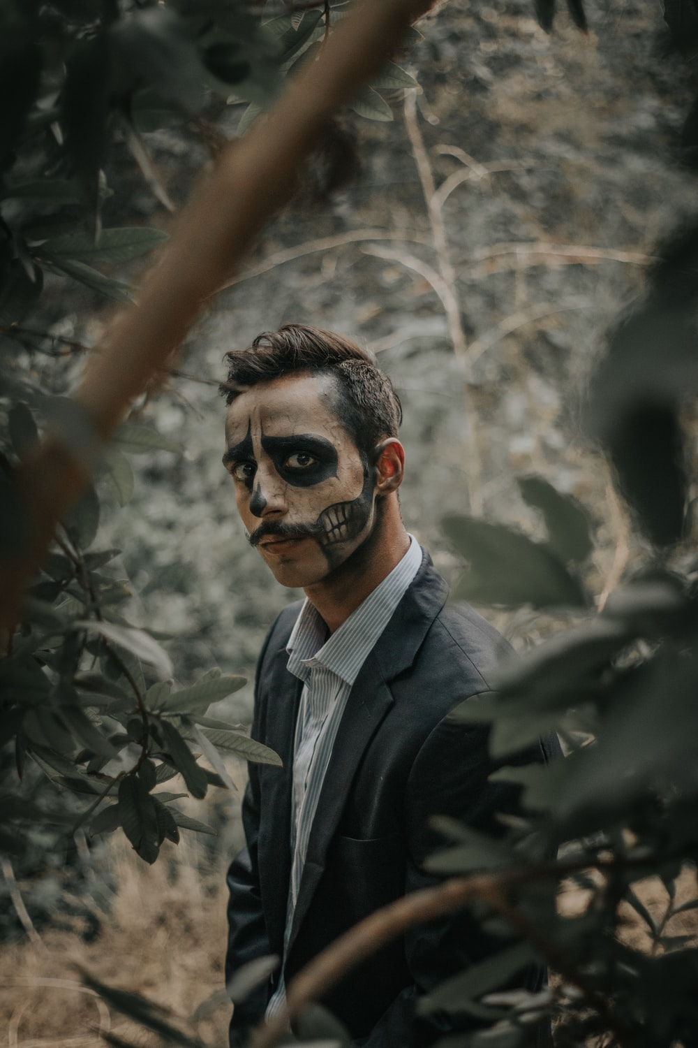 man wearing black notched lapel suit jacket with Halloween face art standing surrounded with tall and green trees