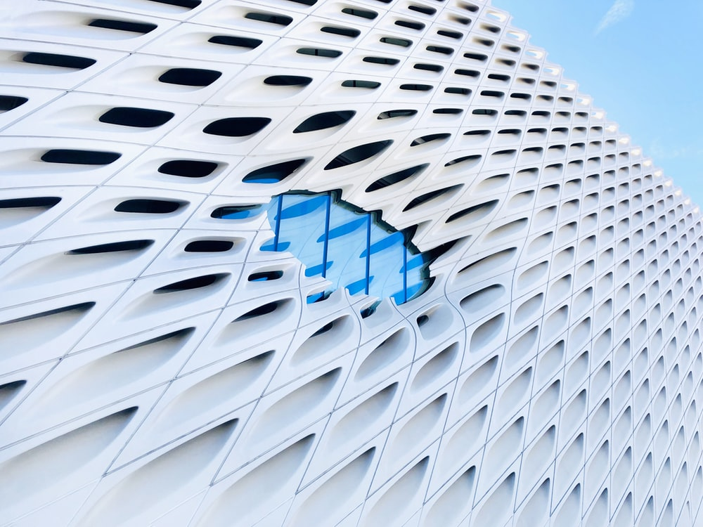 macro photography of white building under blue and white sky during daytime