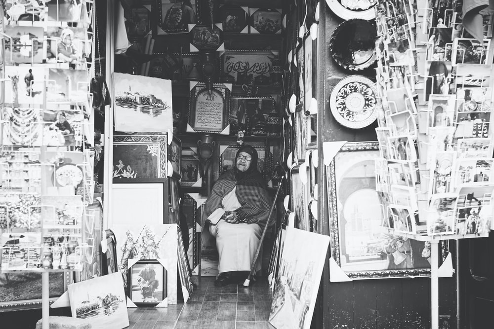 grayscale photography of woman sitting inside store