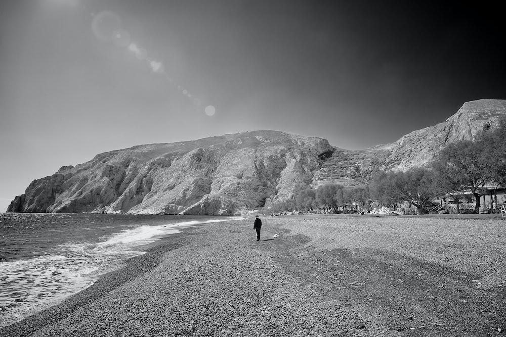 greyscale photo of person walking on seashore