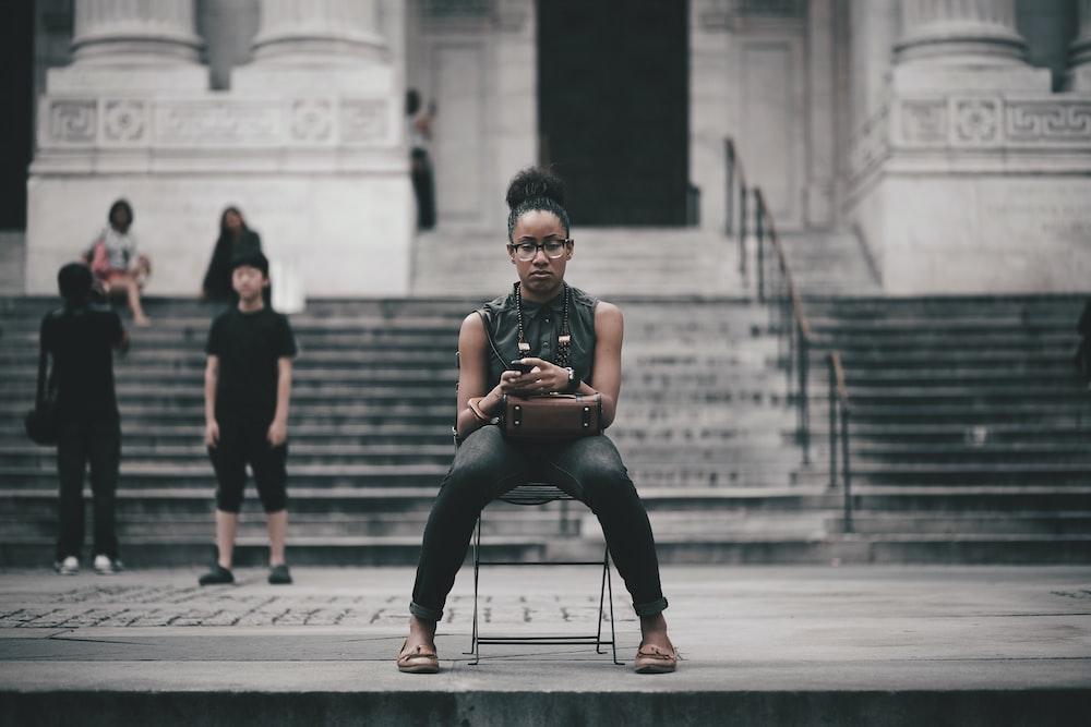 woman sitting on black chair \