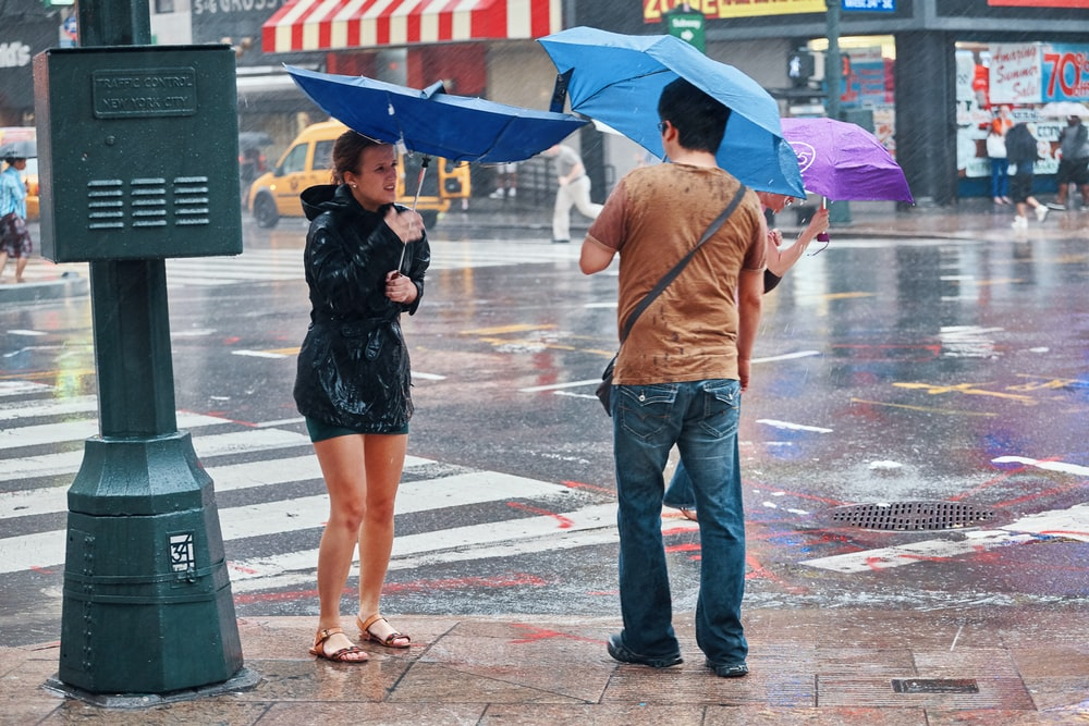 man and woman holding umbrella