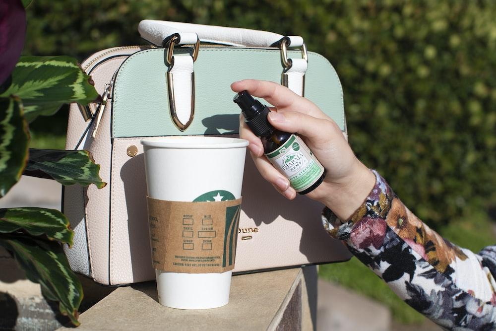 white Starbucks disposable cup beside handbag