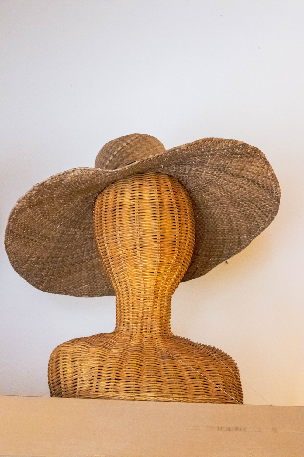 brown strawhat on brown wicker mannequin