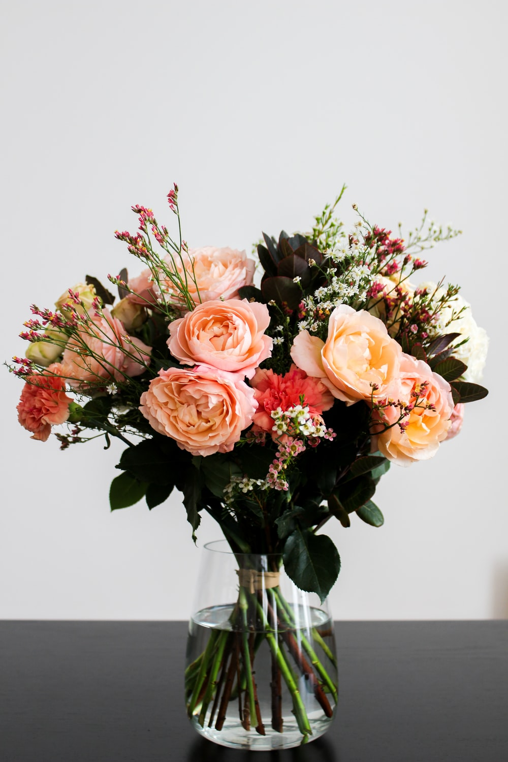 pink, beige, and red flower bouquet in clear glass vase