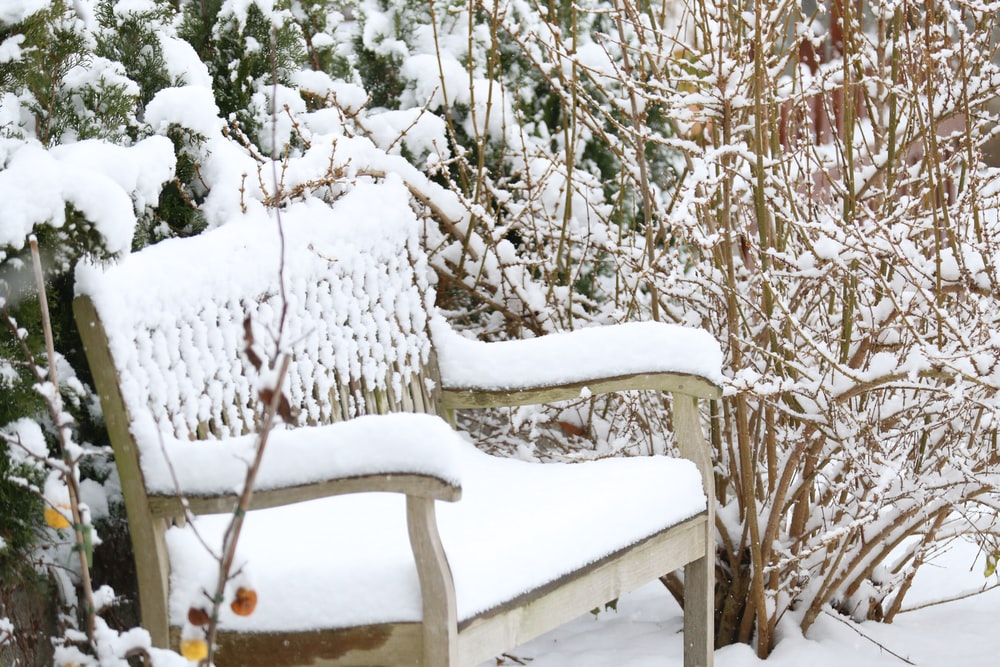 white wooden bench filled with snow