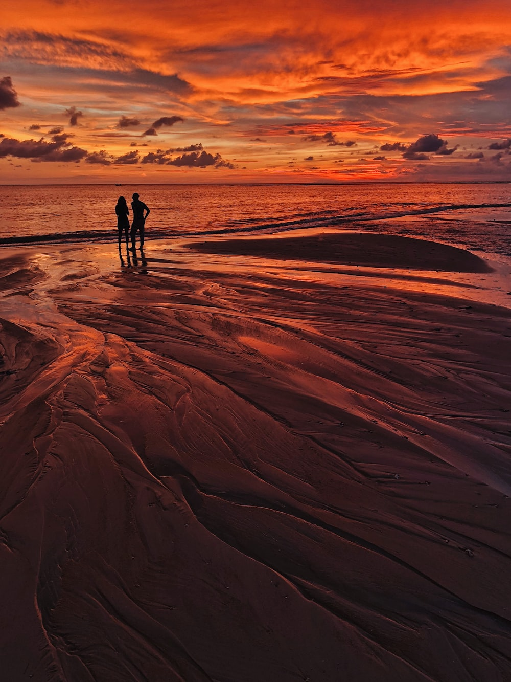 silhouette of man and woman standing on seashore