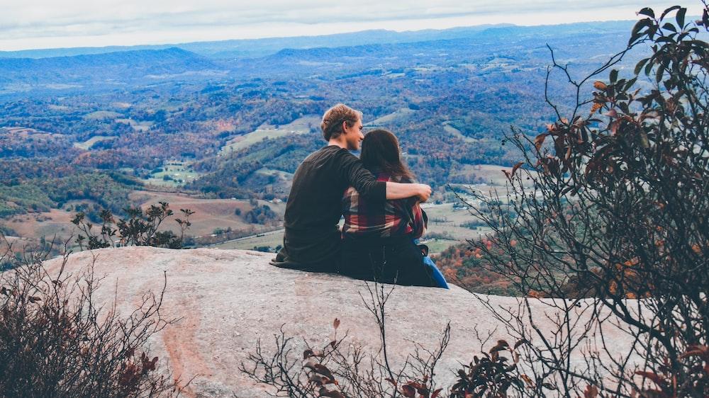 couple sitting on the mountain feld