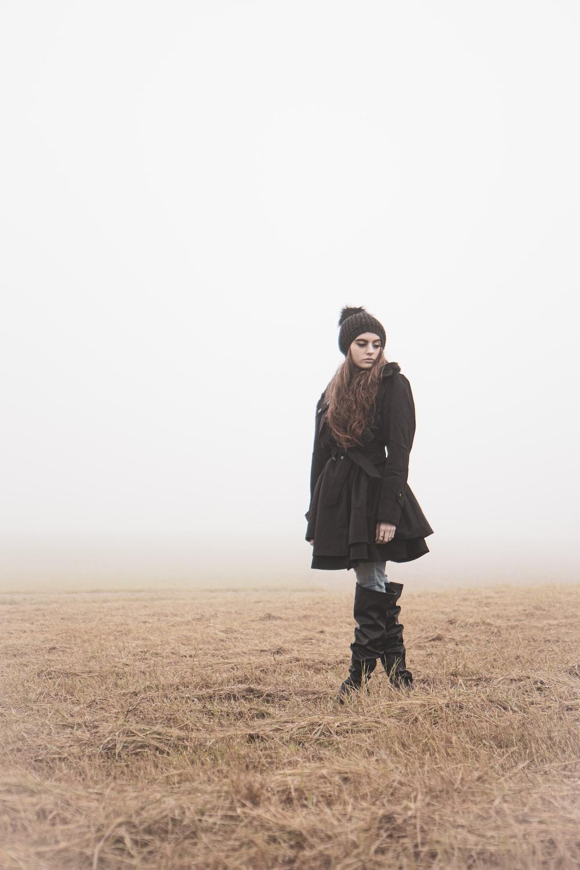 woman standing in an open grass field