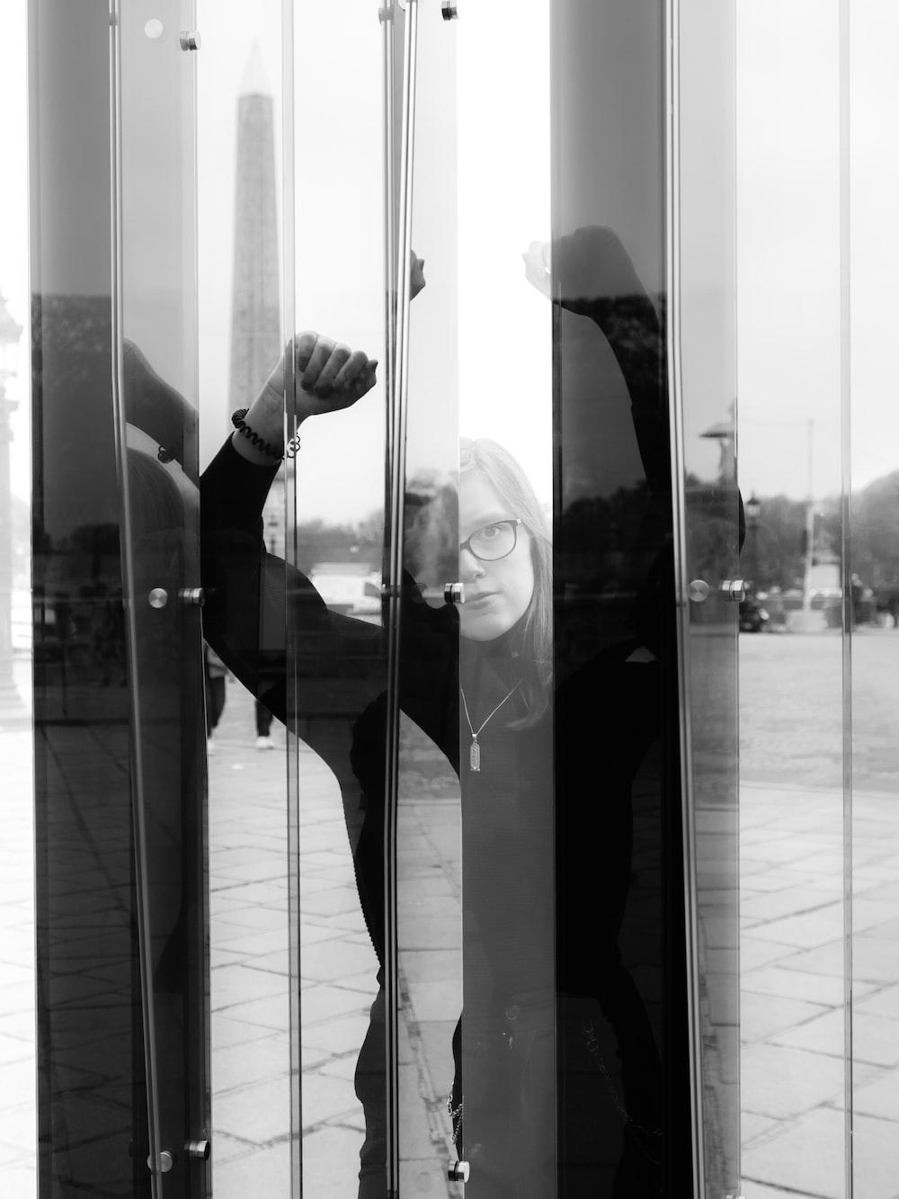 woman near clear glass wall