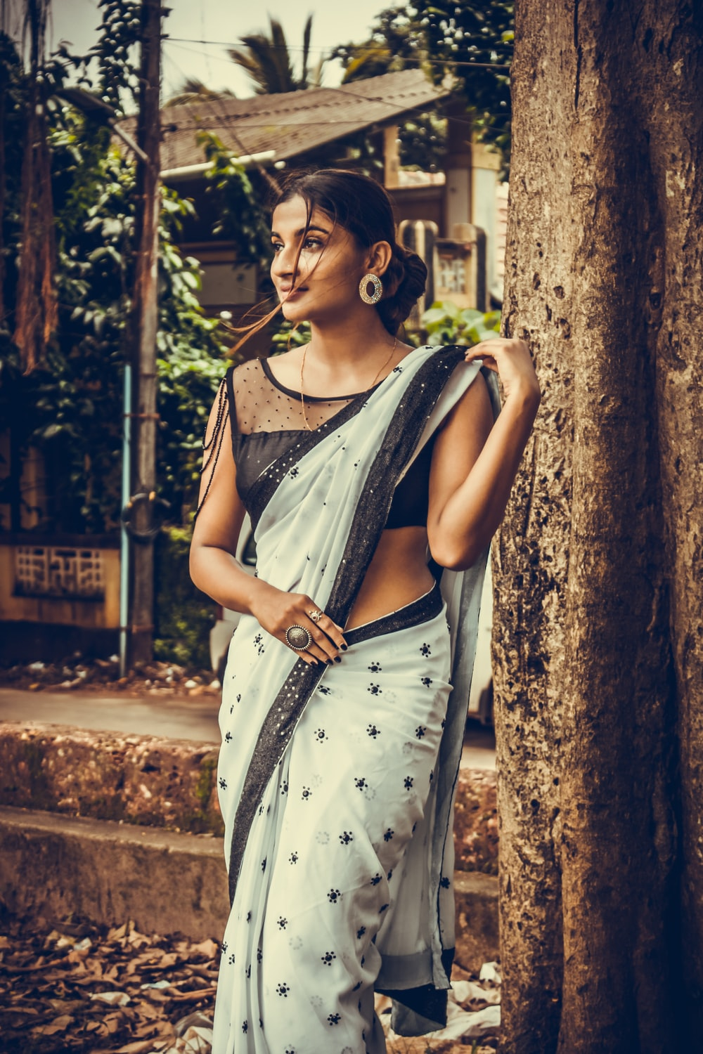 woman wearing black and white saree dress standing on tree