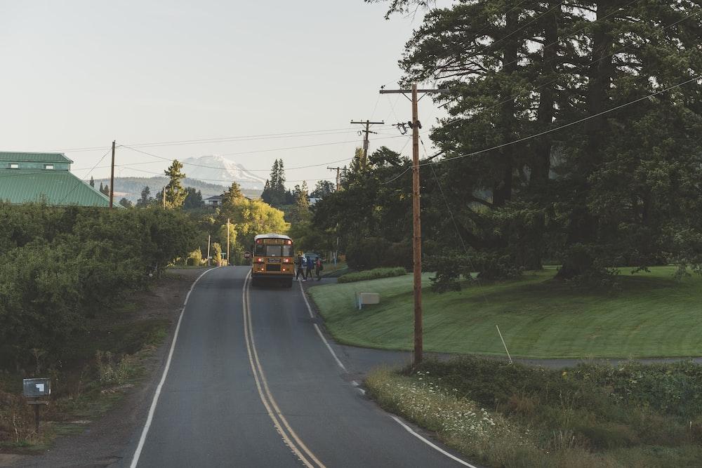 orange bus on road near green field during daytime