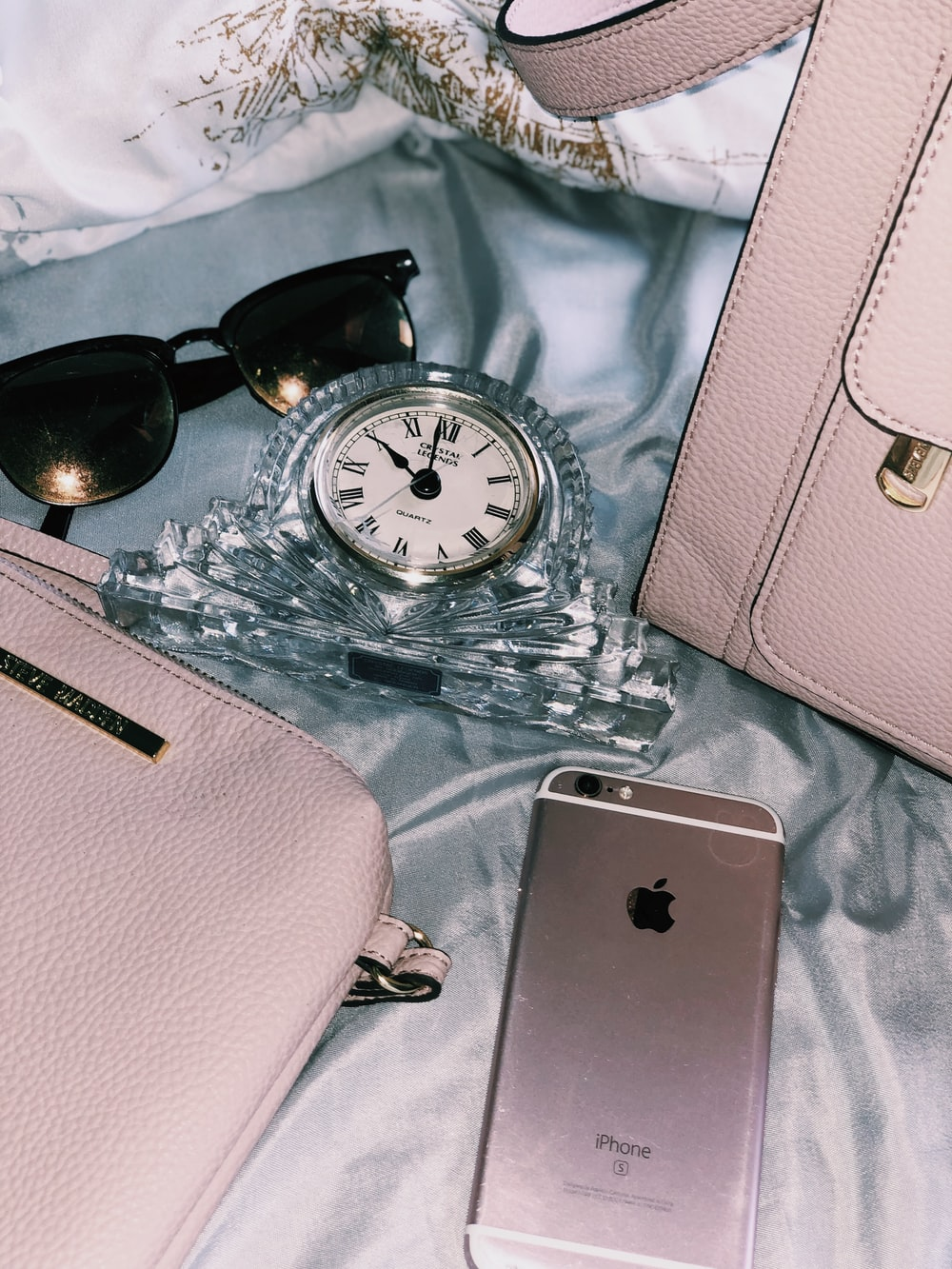 gold iPhone 6s near black framed sunglasses, pink leather bag, and clear analog clock