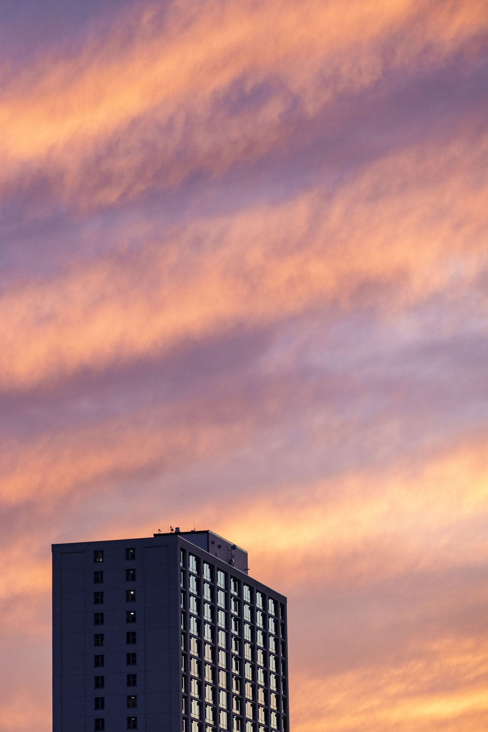 gray high-rise building under a cloudy sky during golden hour