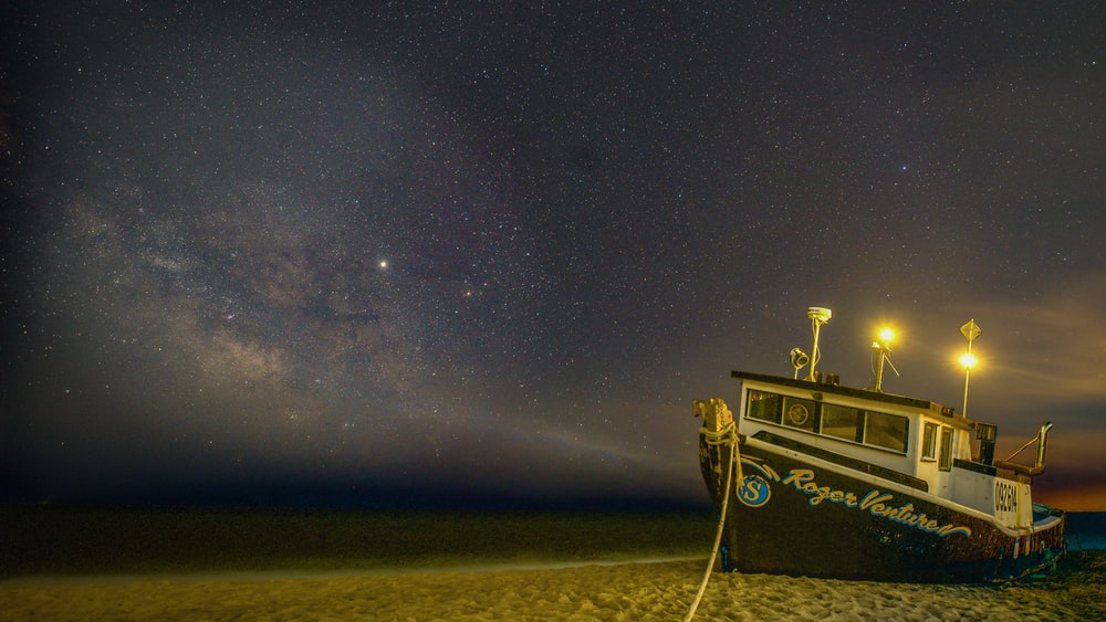 black and white boat on a beach under a starry sky