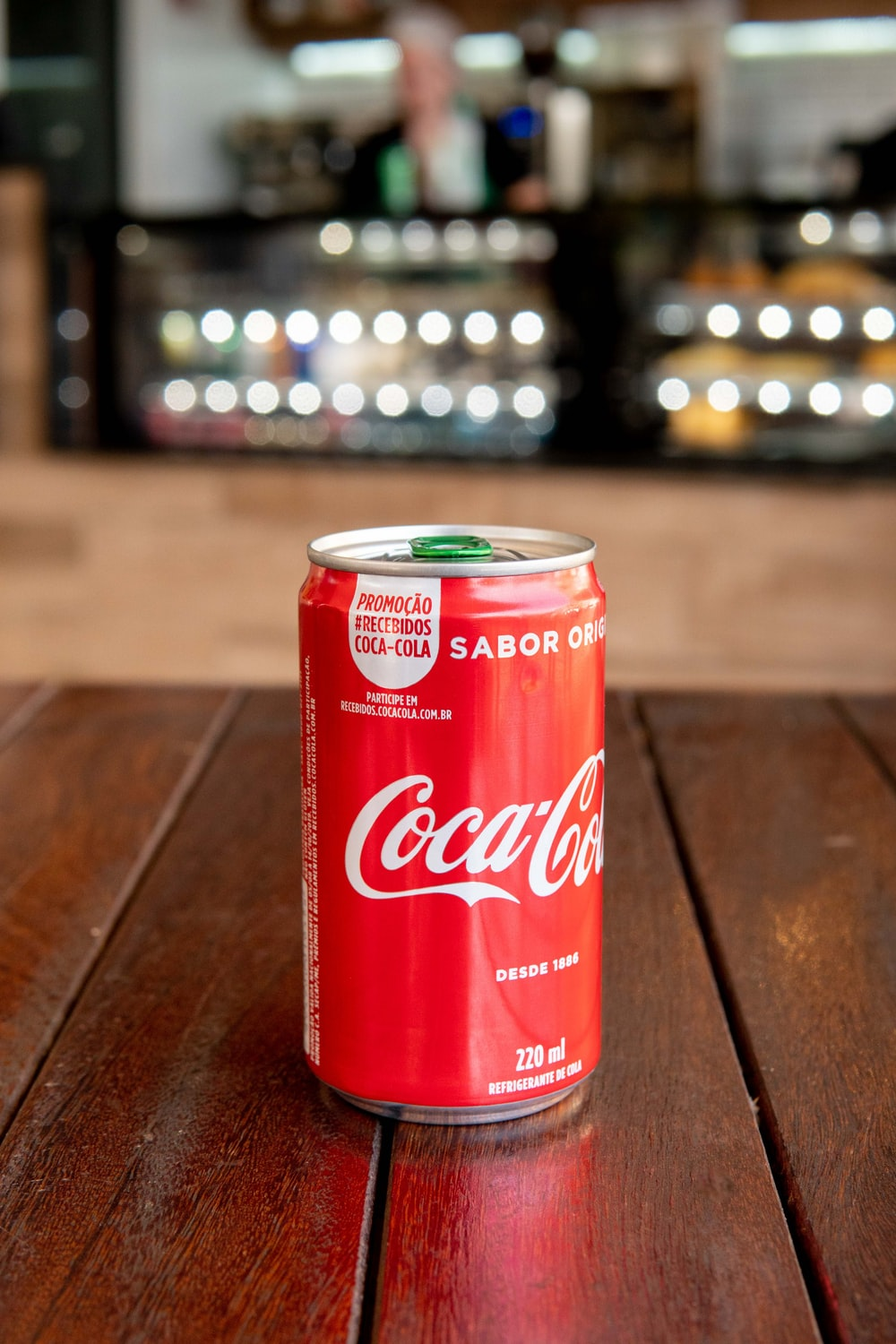 Coca-Cola soda can on brown table