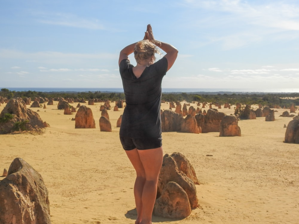 woman wearing black blouse standing near the stone