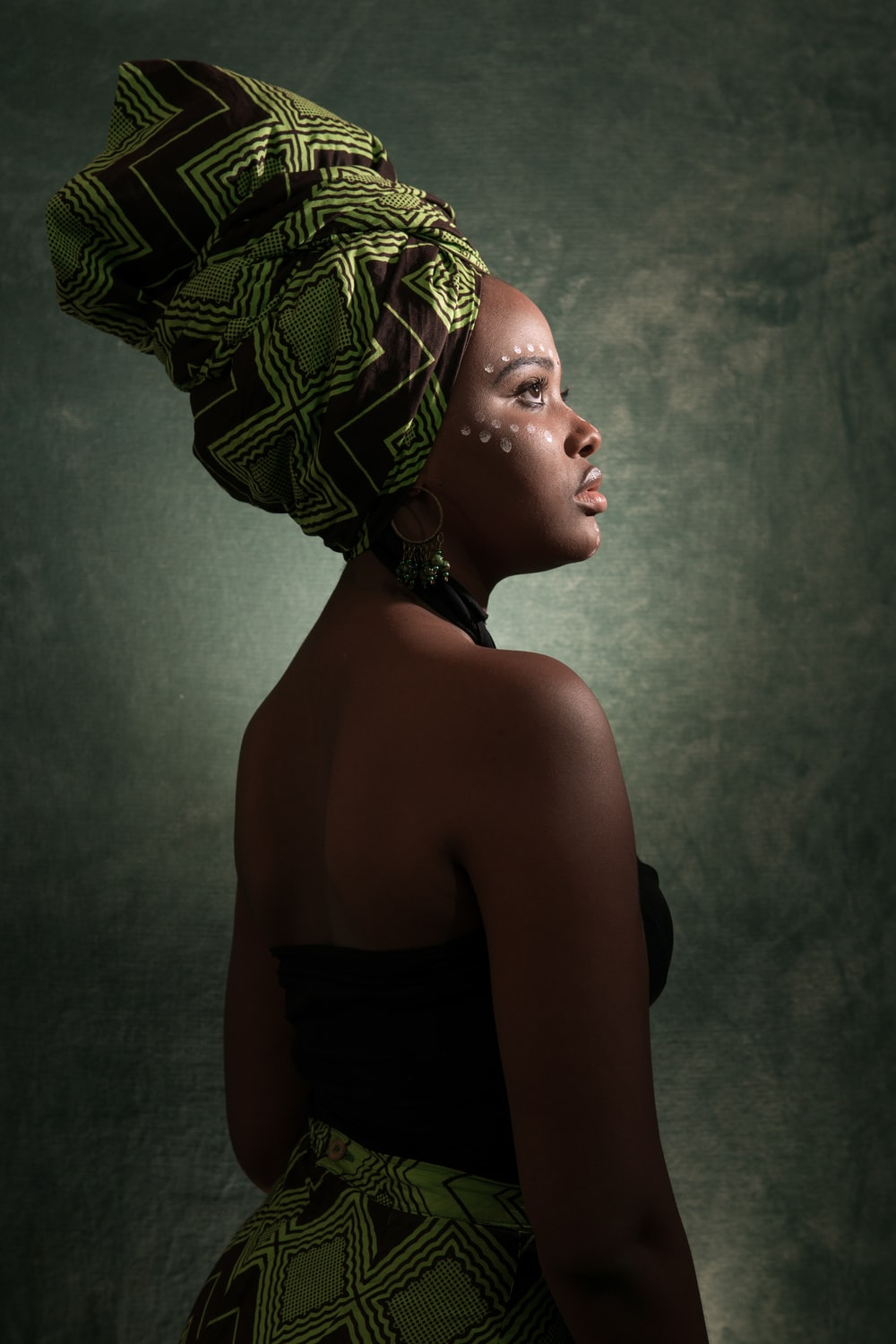 woman in black and green tube-top dress with turban