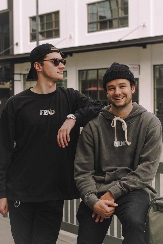 man leaning on smiling man