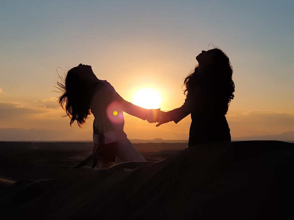 silhouette photo of two women holding each other hands