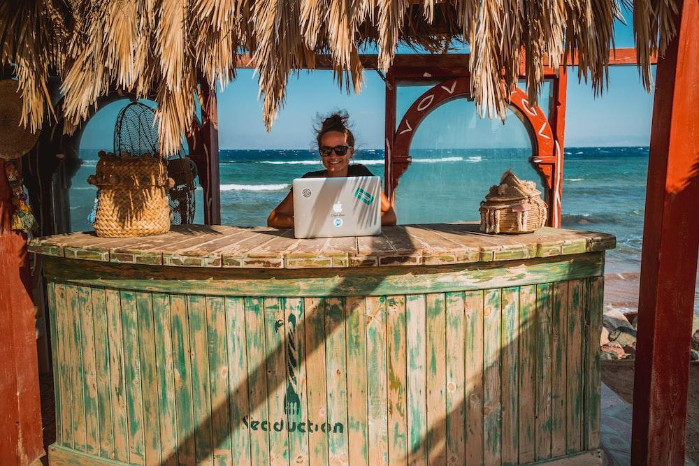 woman sitting on tiki bar facing silver laptop