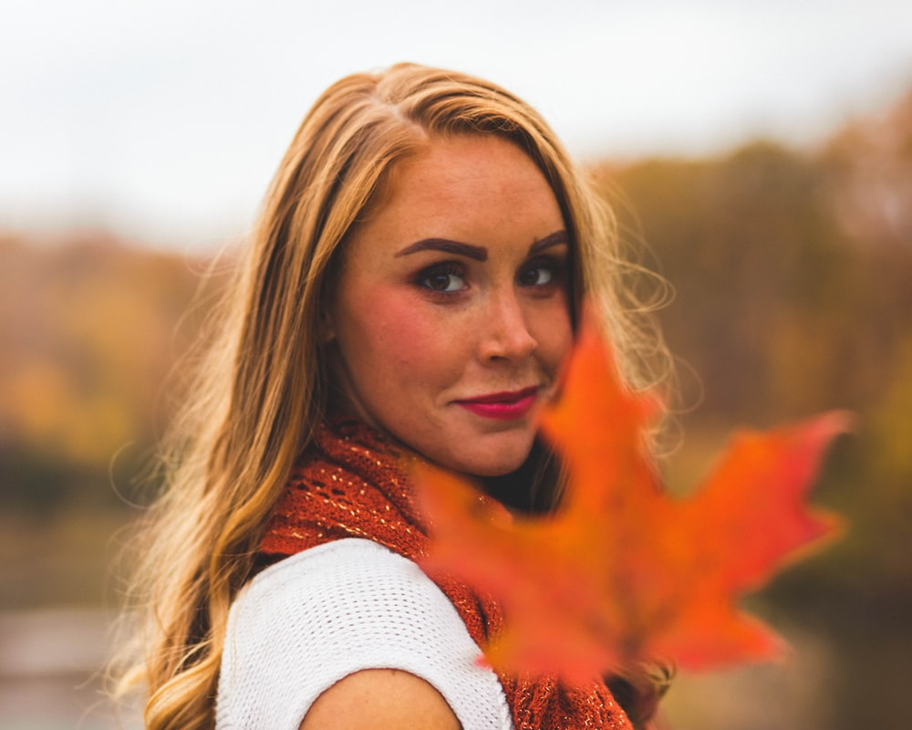woman holding orange maple leaf