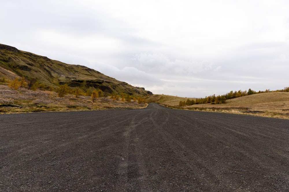 gray concrete road and green mountain