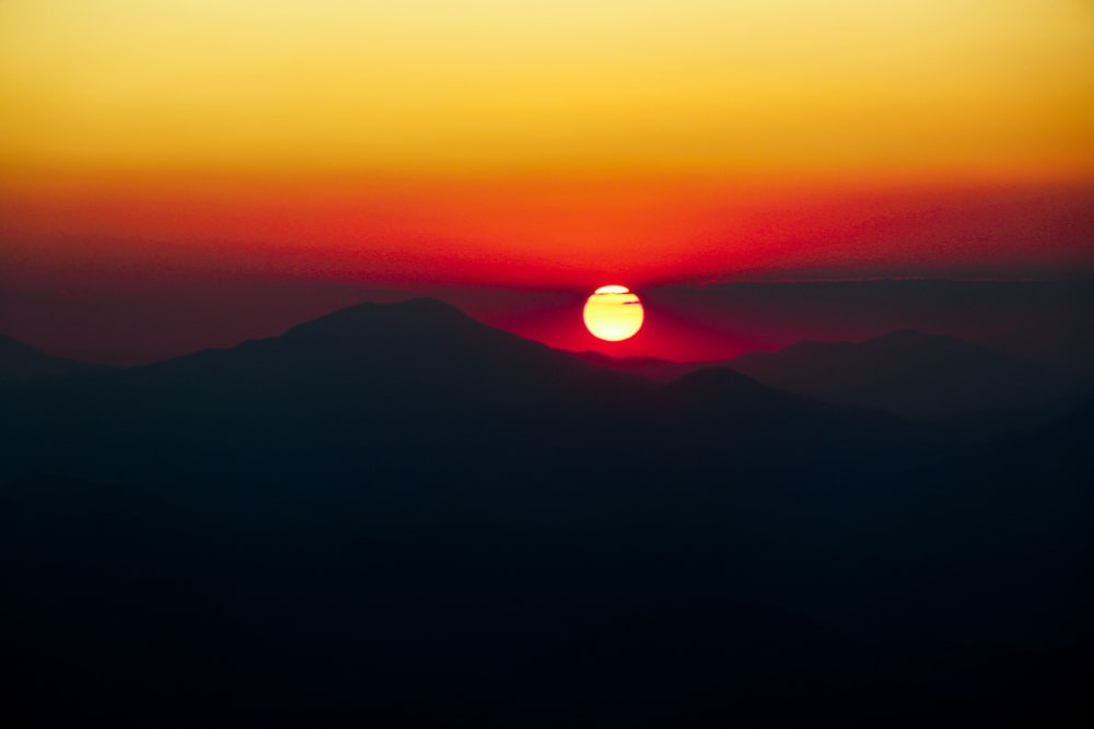 silhouette of mountains and orange sky