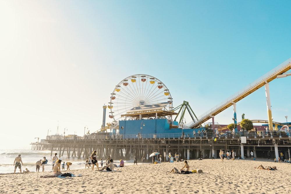 photo of yellow and white Ferris Wheel and seashore