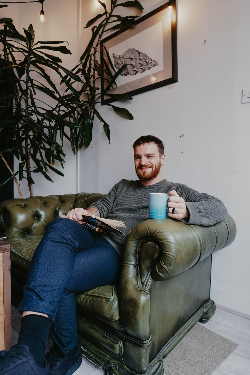 man sitting on brown leather sofa