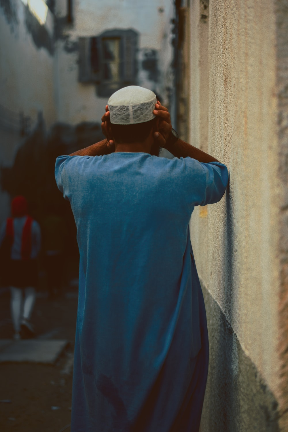 man standing near brown wall holding his head