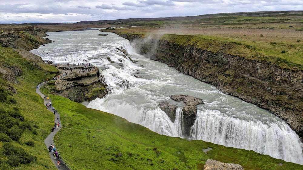 waterfalls beside grass field