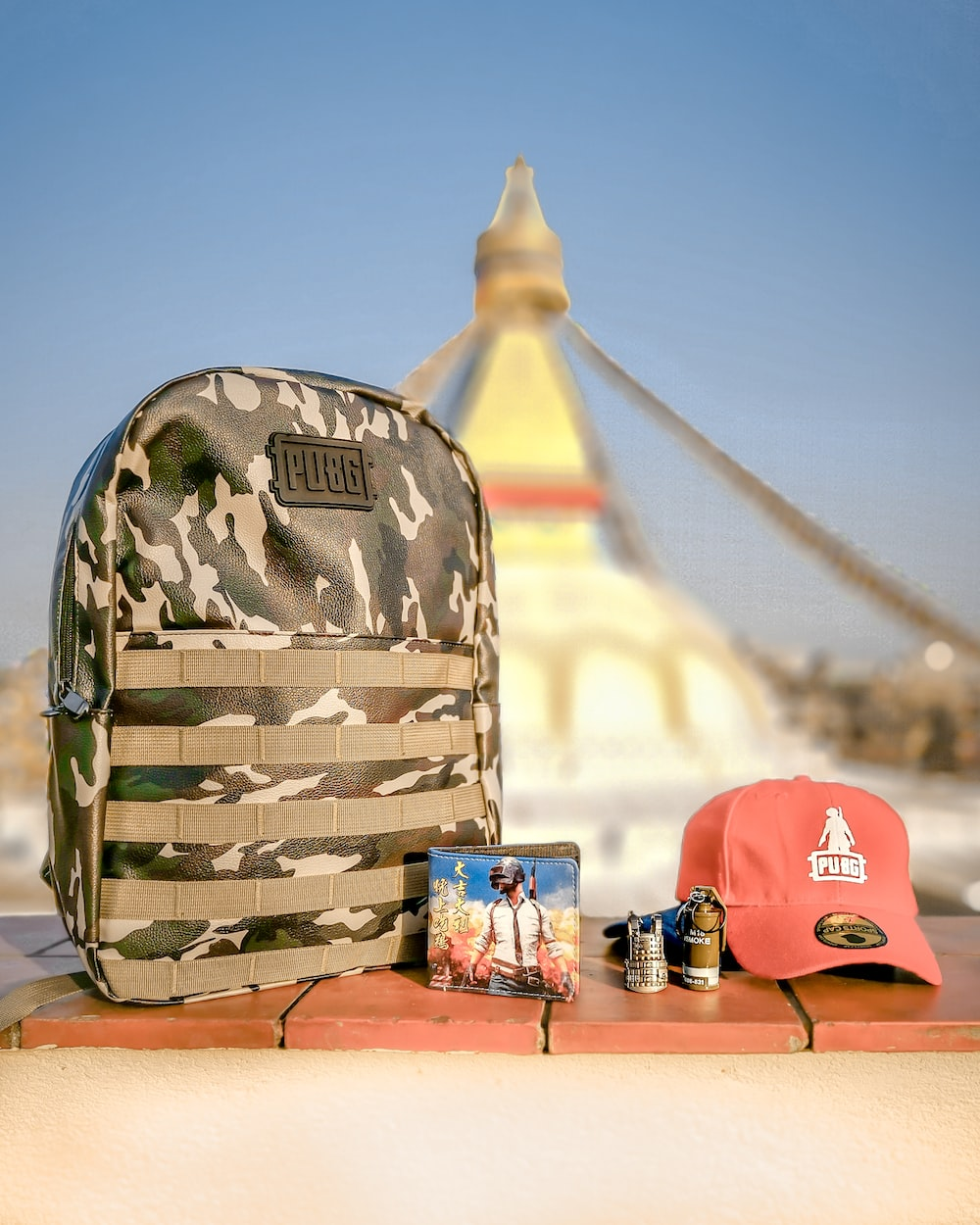 gray camouflage backpack beside cap