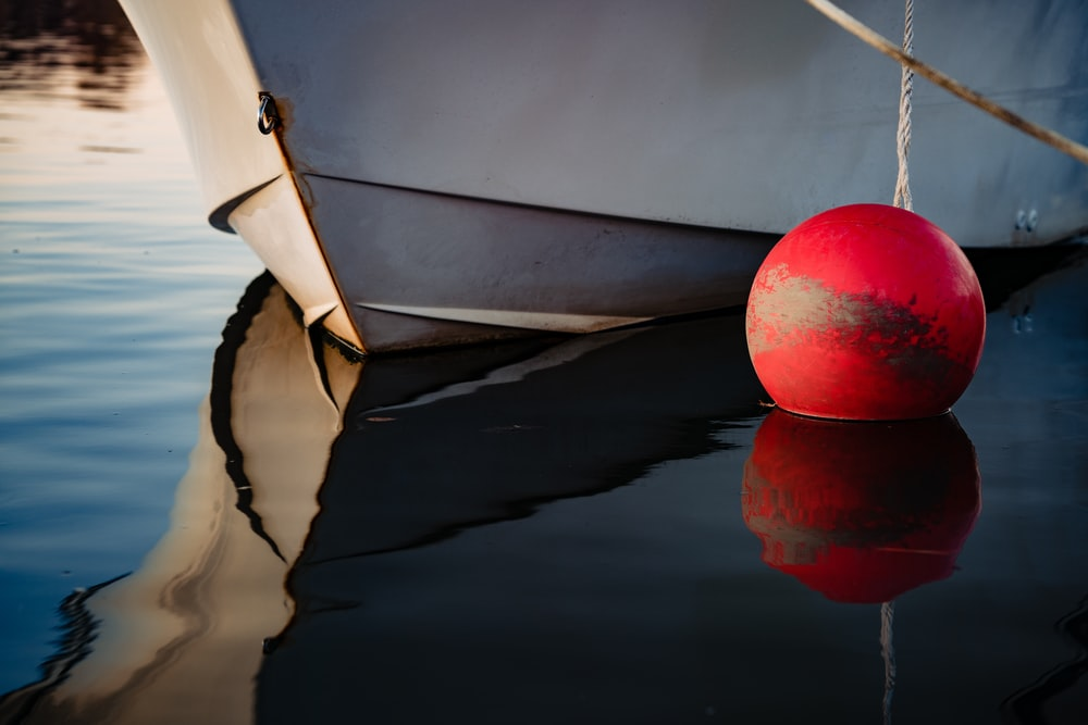 round red floating ball on water beside boat