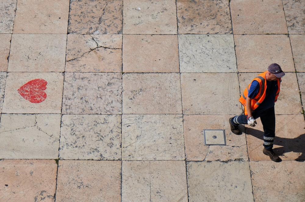 man wearing orange reflective vest walking on pathway during daytime