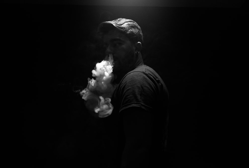 grayscale photo of man exhaling smoke