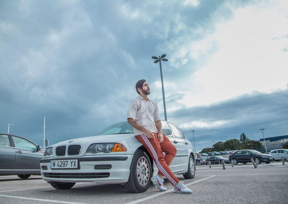 man sitting on white BMW car