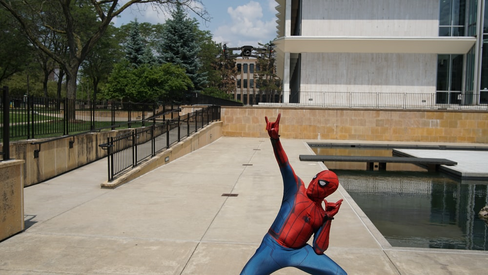 black quadcopter over person wearing Spider-Man costume